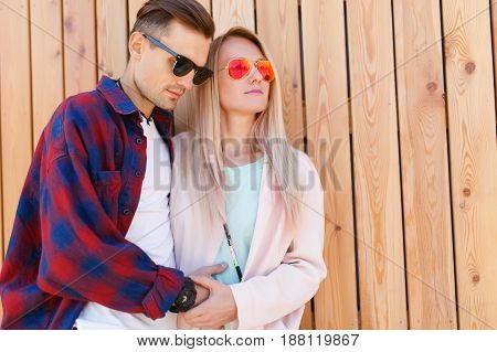 Young lovers embrace on wooden fence background