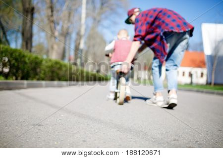Blurred image of father with son and run bike in park