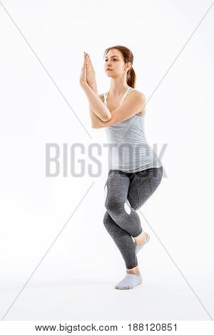 Young woman exercising in balance on blank isolated background