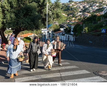 ESTREITO DE CAMARA DE LOBOS PORTUGAL - SEPTEMBER 10 2016: Group of people in traditional costume durnig historical and ethnographic parade of Madeira Wine Festival in Estreito de Camara de Lobos on Madeira Portugal.