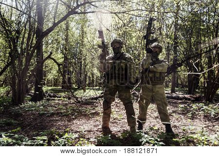 Photo of soldiers with arms in full grown at woods during day