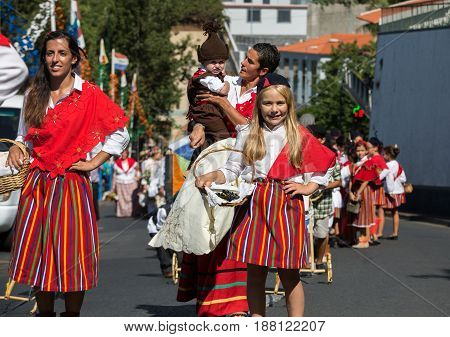 ESTREITO DE CAMARA DE LOBOS PORTUGAL - SEPTEMBER 10 2016: People wearing in traditional costumes at Madeira Wine Festival in Estreito de Camara de Lobos Madeira Portugal. The Madeira Wine Festival honors the grape harvest with a celebration of traditional