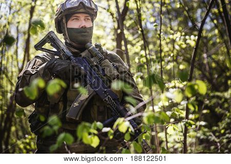 Soldier in helmet on military mission in forest during day