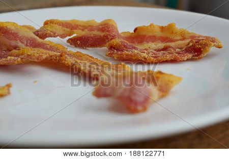 Macro detail of unhealthy crispy bacon strips as a symbol of typical American breakfast food