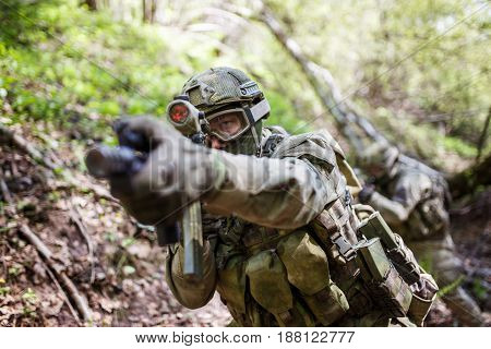 Photo of aiming military man with gun in woods during day