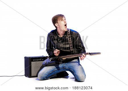 young expressive handsome rock musician playing electric guitar and singing. Rock star