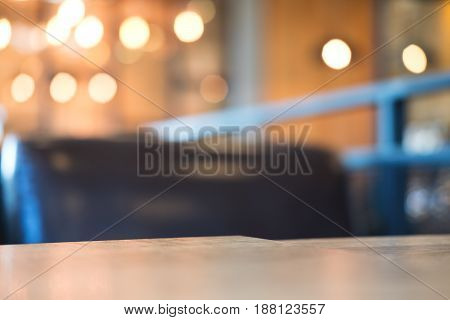 Wooden table and chair in cafe with blur bokeh abstract vintage background