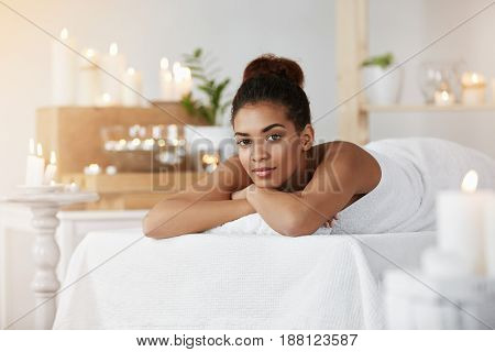 Young beautiful african girl looking at camera resting relaxing in spa salon. Copy space.