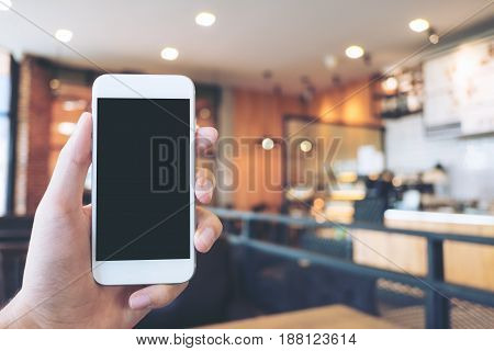 Mockup image of hand holding white mobile phone with blank black screen in modern loft cafe