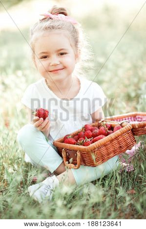 Smiling child girl eating fresh strawberry in park. Looking at camera. Childhood.