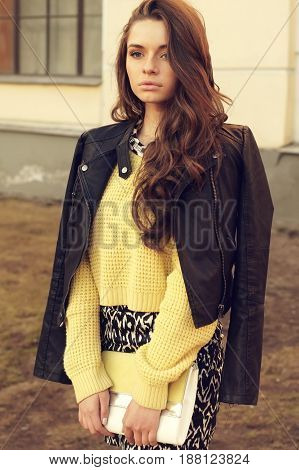 young beautiful woman wearing dress, yellow pullover and leather jacket posing outdoors. stylish fashion portrait