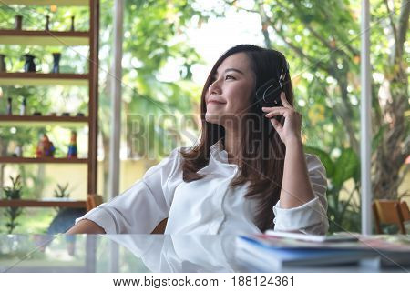 A beautiful asian woman listening to music with headphone in cafe with feeling relax and green nature background