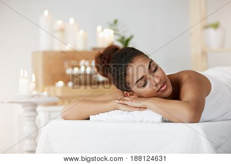 Young tender african girl resting relaxing with closed eyes in spa salon.