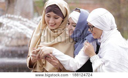 Beautiful Muslim Girl Using Smartphone and Laughing.