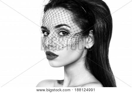 closeup fashion portrait of young beautiful woman wearing black veil isolated on white background. Black and white colors