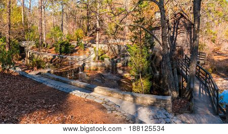Panoramic view of the Grist Mill and creek flowing into the lake in the Stone Mountain Park in sunny autumn day Georgia USA