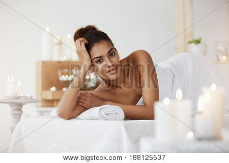 Young attractive african girl relaxing in spa salon looking at camera smiling.