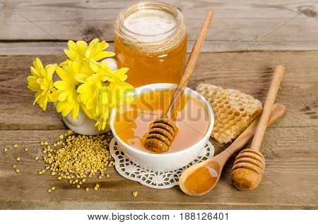 Yellow Flowers And Bee Products (honey, Pollen, Honeycombs) On Wooden Background