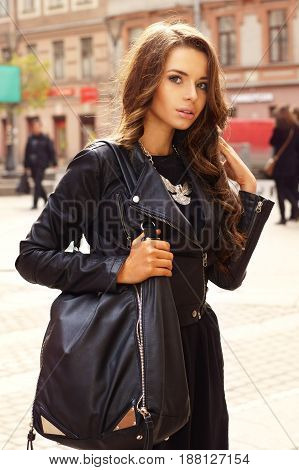 portrait of young stylish girl in black dress and black leather jacket holding big black bag and standing at the street