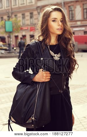 outdoor portrait of young beautiful stylish girl in black dress and jacket