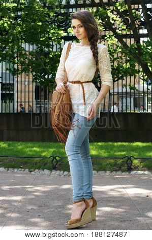 full lenght outdoor portrait of young beautiful stylish girl in blue jeans and lace blouse
