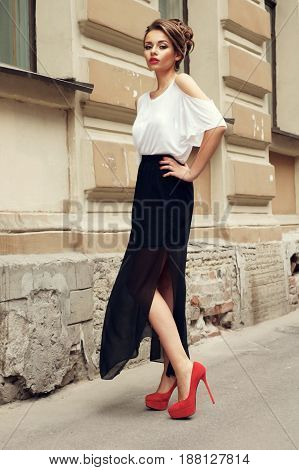 outdoor portrait of you beautiful stylish girl wearing long black skirt and white t-shirt