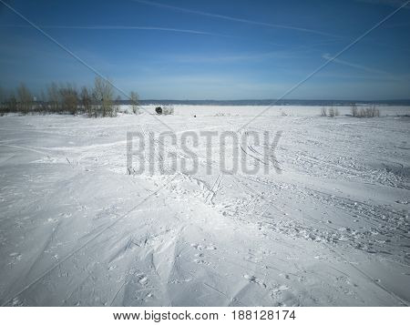 Beach in winter in Siberia. Snow and ice on the sea to the shore in the distance with trees. Trail from an airplane in a blue sky