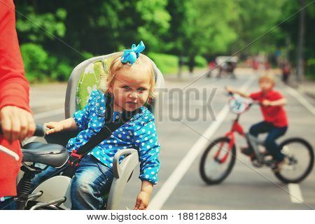 mother with two kids riding bikes in the city, active family