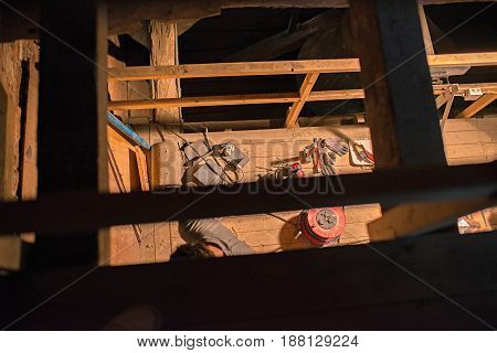 Top View Of Tools And Electricity Parts Lying On Wooden Floor In Attic Of Church. Restoration Work.
