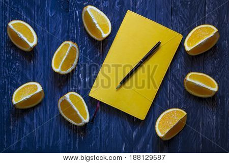 Yellow notebook and black pen with cut oranges on blue wooden background flat lay