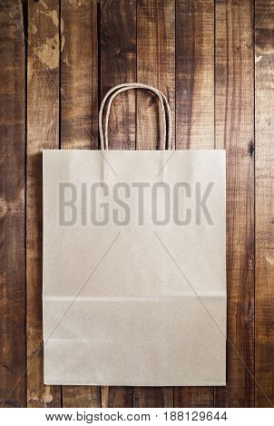 Recycled craft shopping bag on vintage wooden table background.