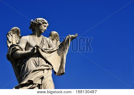 Angel statue holding the Holy Veil on Sant'Angelo Bridge in Rome (with blue sky and copy space)
