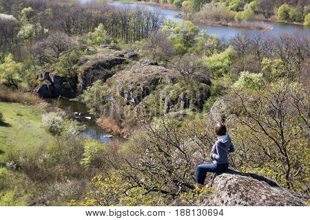 Caucasian Female Sitting On A Big Stone Above The River And Forest, Spring Time