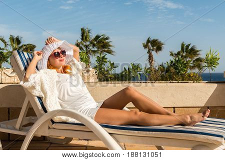 Young woman enjoying sun on sunbed at tourist resort