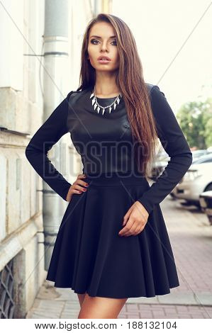 beautiful stylish sexy girl in black dress posing at the street