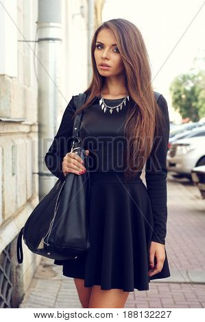 portrait of stylish beautiful girl wearing short black dress posing or walking at the street