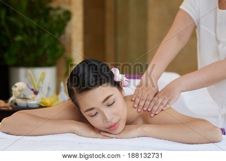 Unrecognizable massage therapist carrying out procedure in modern beauty salon, pretty young woman relaxing on massage table with closed eyes