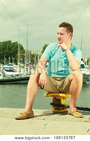 Summertime vacation adventure concept. Man spending his free time walking on marina sightseeing during summer guy sitting on bitt.
