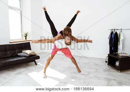 Young beautiful sportive couple practicing partner yoga asanas at home. Copy space.