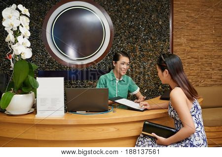 Pretty Asian receptionist with charming smile showing price list of beauty salon to young client, waist-up portrait