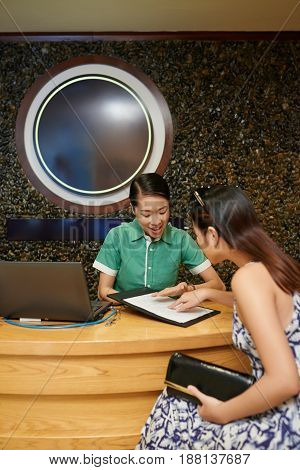 Waist-up portrait of friendly Vietnamese receptionist showing available procedures and costs to female client in spa salon