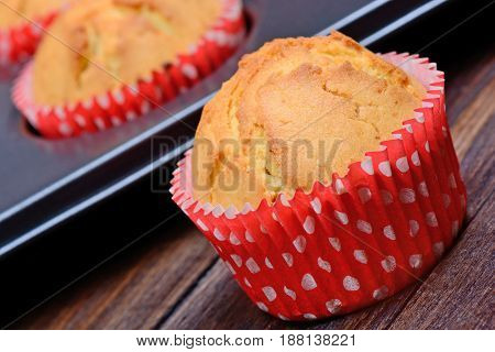 Tray with muffins on wooden table closeup