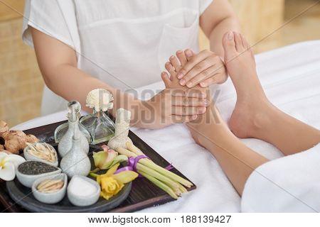 Unrecognizable therapist doing foot reflexology massage at luxurious spa salon