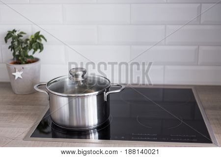 Cooking Concept - Close Up Of Metal Pot On Electric Or Induction Stove In Kitchen