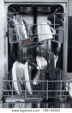 Close Up Of Open Dishwasher With Clean Utensils In Kitchen