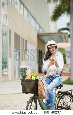 Beautiful middle-aged bicyclist texting with friend on smartphone while standing on parking lot of shopping mall, groceries lying in bike basket