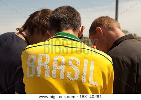 Khabarovsk Russia - May 21 2017: Brasil text on the back of yellow sport shirt - young athletes talking back view. 3 players discussing game strategy during timeout. Brazil country name written on the sportswear