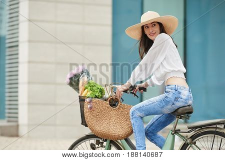 Middle-aged woman with charming smile riding bicycle after shopping for groceries, full length portrait