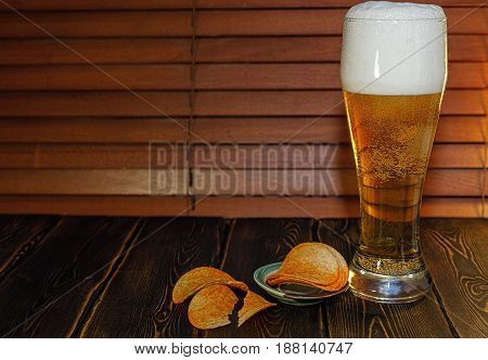 A large glass of beer and potato chips. On the wooden table stands just poured a glass of beer. High foam in the glass. Light beer. White foam on the beer.