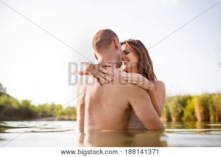 Happy young loving couple embracing and smiling in the lake.